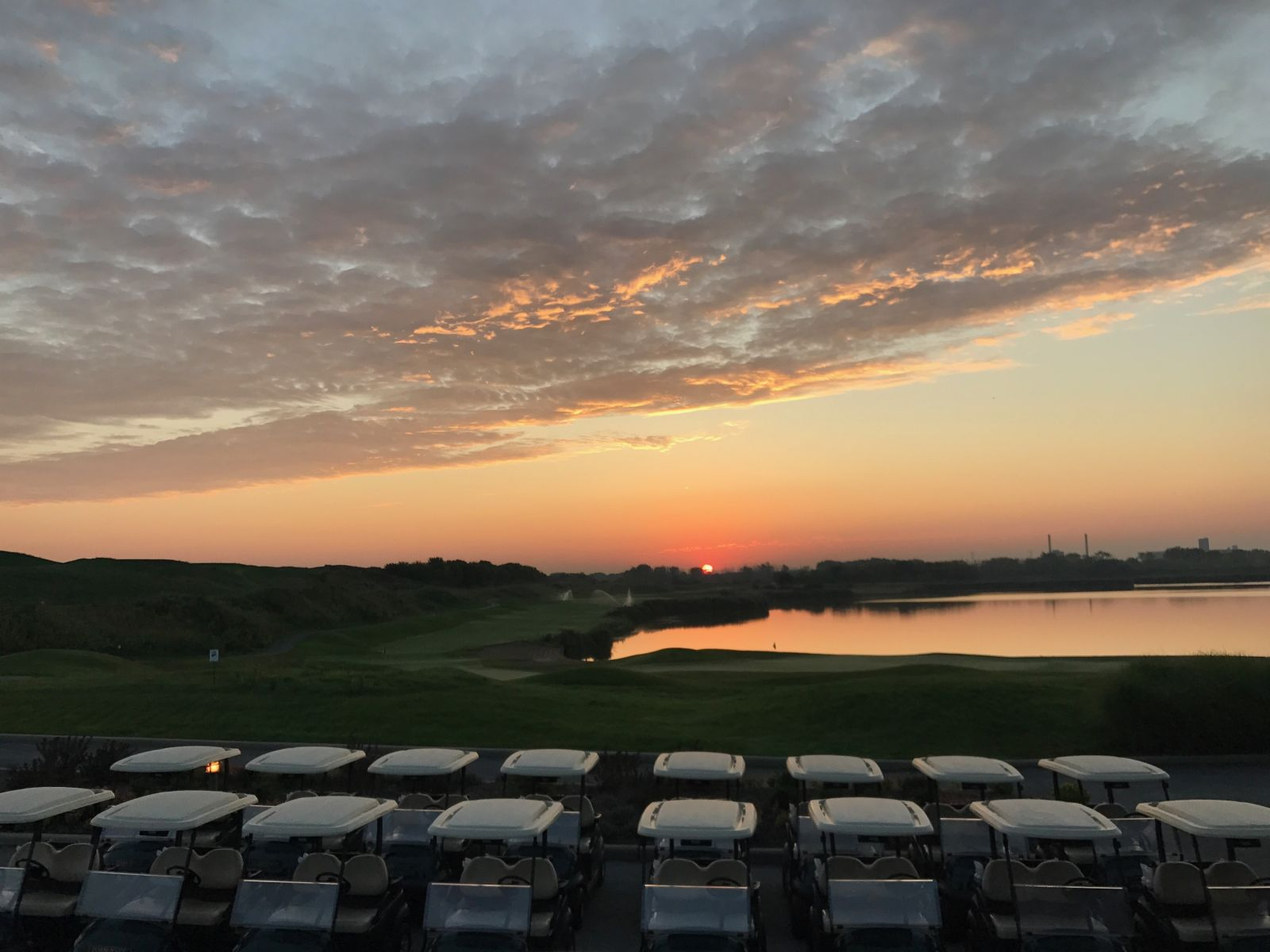 The sun sets over a fleet of golf carts at Harborside International Golf Center